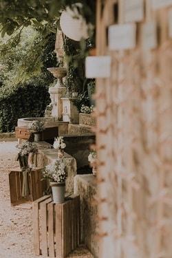 décoration de mariage bohème, vielle caisse en bois et fleurs blanches au bord d'une fontaine en provence