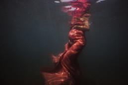 photo femme grossesse dans la mer à Frontignan à côté de Montpellier. Femme enceinte dans l'eau avec un voile rose sur le corps qui moule son ventre rond, 7 eme mois de grossesse