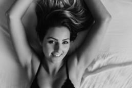 portrait femme qui souris allongé sur le lit vue du dessus, portrait en noir et blanc