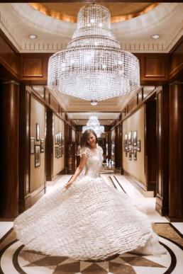 mariée qui fait tourner sa robe dans un hôtel de luxe avec lustres en cristal de baccarat