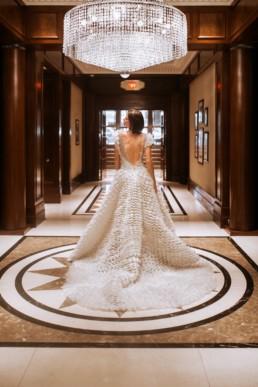 mariée de dos dans le hall de l'hôtel de luxe avec lustre en cristal, à new york. robe de mariage gemy maalouf