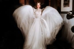 la mariée qui joue avec sa robe de mariage en tulle, haut transparent en dentelle