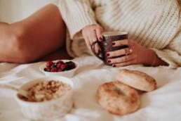 femme qui tiens sa tasse de thé, avec bols de fruits rouges et céréales. Vernis rouge aux mains