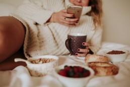 femme sur le lit qui regarde son téléphone devant son petit déjeuner avec des céréales et des fruits