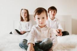 trois enfant frères et soeurs qui posent pour des photos de famille. Chemise blanche et jeans bleu