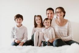 trois enfants et leurs parents qui posent une une photo de famille a paris.