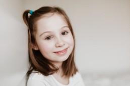 portrait d'une petite fille avec une couette, rousse aux yeux verts