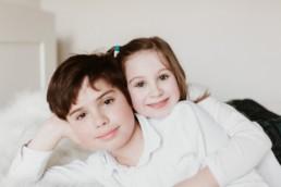 portrait d'un grand frère et de sa petite soeur qui se tiennent dans les bras à Lavérune