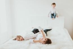 des enfants qui jouent sur le lit et font des grimaces à clapiers pour une séance photo