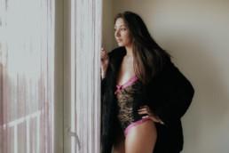 femme sexy brune cheveux long et manteau en fourrure attends devant la fenêtre. Body dentelle noir