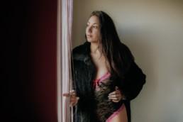 femme brune en fourrure et body en dentelle devant la fenêtre