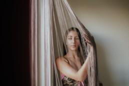 femme qui joue avec les rideau de sa fenêtre à Montpellier.