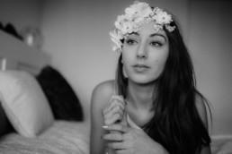 photo en noir et blanc d'une femme sur le lit qui réfléchi, fleurs blanches sur le front