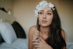portrait femme brune fleurs blanches sur le front, qui réfléchi