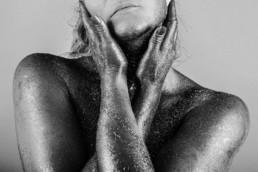 photo noir et blanc d une femme bras croisés sur le coup, la peau avec des paillettes