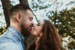 bisous sur la bouche pour un couple avec barbu, et chemise en jean, dans la nature à montpellier