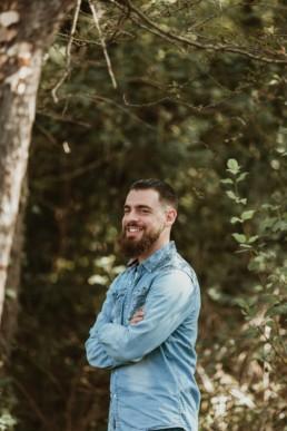 portrait d'un homme barbu souriant qui croise les bras. Chemise en jeans bleu clair à Montpellier