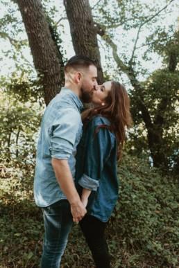 bisous d'amoureux dans la nature. Chemises en jeans, barbus, brun