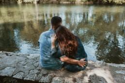 couple en jeans assis devant une rivière à Montpellier