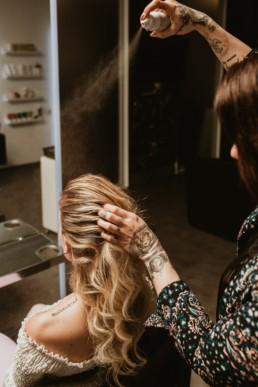 coiffeuse a montpellier qui met de la laque dans les cheveux d'une blonde