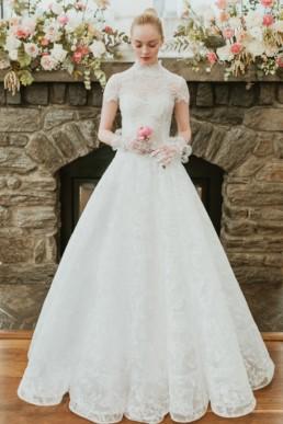 robe de mariée blanche classique et sophistiquée en dentelle, avec gants de mariage et fleurs rose dans les main. Défile de robes isabelle armstrong new york