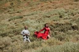 shooting de mode avec un couple black. Robe rouge fendu et sexy qui vole au vent. homme costume de luxe