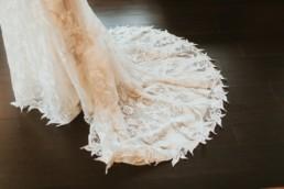 photo détail de la traine de la mariée, motif fleur et feuille
