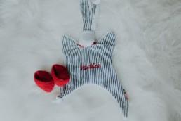 doudou et chaussons rouge tricote a la main posé sur le lit, pour futur bébé mathéo