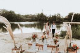 décoration de mariage d'automne au bord de l'eau. Décoration de pampa, table de mariage. Repas de mariage sur le sable. Fleurs de mariage, bouquet de mariage en pampa et roses orange. Robe de mariée bustier, fente sur la cuisse