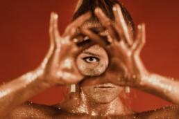 femme recouverte de paillette en or formant un cercle avec ses mains et son oeil est dans le cercle