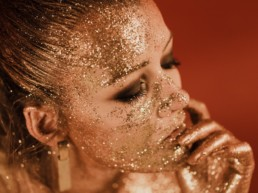 femme blonde recouverte de paillettes, maquillage des yeux smocky marron et noir, piercing au nez