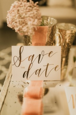carton d'invitation de mariage save the date avec calligraphie en or. ruban de mariage rose oranger