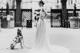 une future mariée en robe blanche longue et son chien un dalmatien avant la ceremonie de mariage a new york