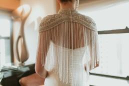 boléro de mariage a perle et sequin, mariée de dos en robe sirène en soie