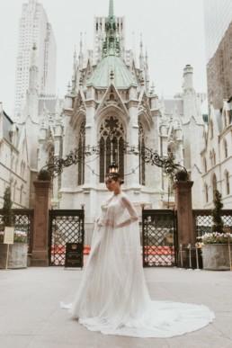 robe de mariage a paillette avec une longue cape devant une église a new york