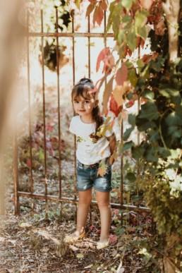 petite fille contre une grille de jardin, entourée de feuille d'automne à avignon