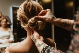 coiffeuse aux mains et bras recouvert de tatouages. Coiffeuse qui fait un chignon sur une femme blonde a montpellier