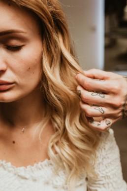main tatoué d'une coiffeuse dans les cheveux ondulés d'une blonde aux cheveux longs