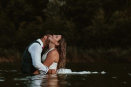 comme qui embrasse sa femme dans le coup pendant la séance photo couple après le mariage à agde. couple de mariés dans l'eau, robe de mariage qui flotte