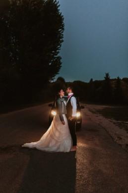 couple de marié devant les phares d'une voiture la nuit a bali, pour une séance photo couple apres le mariage