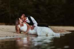 couple de mariés allongés sur le sable les pieds dans l'eau, qui s'embrassent à Cannes