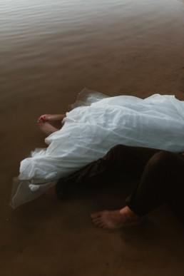 couple de mariée les pieds dans l'eau a frontignan. Robe de mariage et costume du marié dans l'eau