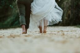 mariées pieds nu qui marchent dans le sable à la grande motte, pour la séance photo couple apres le mariage