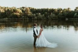 mariés face a face qui se tiens la main pour le day after de mariage a montpellier, costume de mariage avec noeud papillon rose
