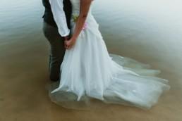 les mains des l'une dans l'autre, les mariés les pieds dans l'eau dans un lac a cote de paris