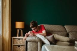 photo d'un adolescent sur le canapé qui joue avec son téléphone