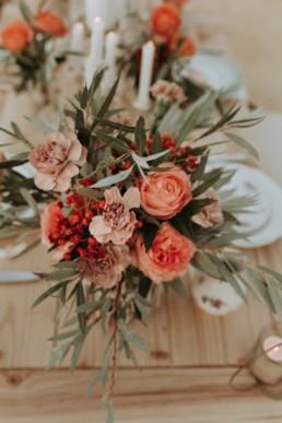 bouquet décoration de table de mariage. Rose orange, feuille d'olivier. Décoration de mariage d'automne