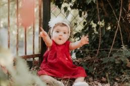 bébé fille étonné bras tendu, robe rouge, bandeau fleur dans les cheveux