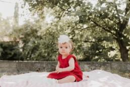 Portrait de bébé fille 1 an . Robe rouge d'été et bandeau grosse fleur sur la tête