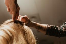 les mains d'une coiffeuse tatoué, qui fait une coiffure de mariage à une future mariée de montpellier